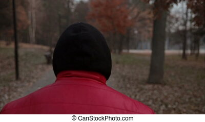 man walking along a alley. view from the back. - man in a...