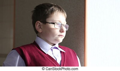 boy with glasses looking out the window HD