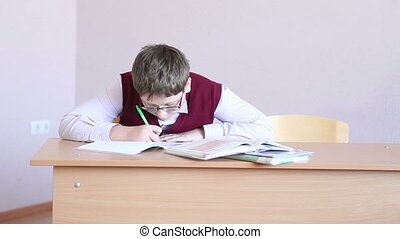 boy with glasses writes in a notebook sitting at a desk