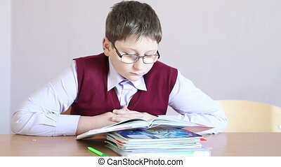 boy with glasses reading a book while sitting at a desk