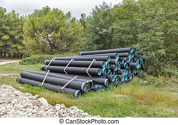 Construction pipes at a construction site in the forest -...