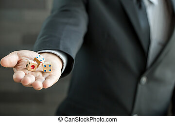 Businessman holding three dices