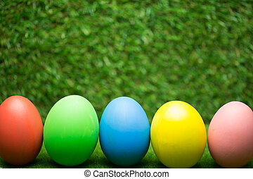 Row of Easter eggs on grass