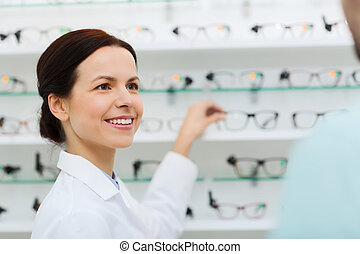 optician showing glasses to man at optics store - health...