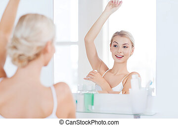 woman with antiperspirant deodorant at bathroom - beauty,...