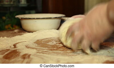 woman knead the dough on the table, close-up