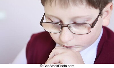 boy with glasses reading a book and rubs his eyes hands