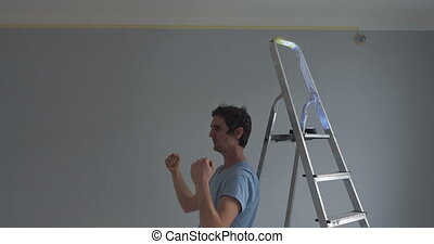 Man visualising something on the wall in a newly decorated...