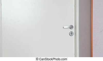 boy with glasses looks into the room through the door