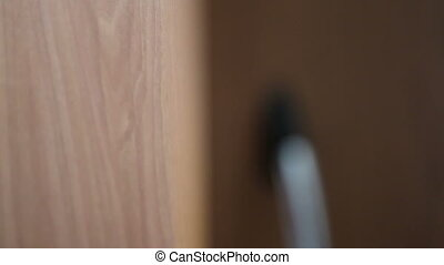 Woman closes bookcase with a key, close-up