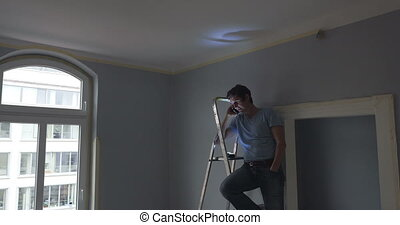 man on ladder making phone call