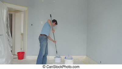 worker painting wall in apartment - man work in his...