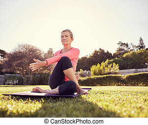 Active senior woman doing a yoga twist outdoors - Low angle...