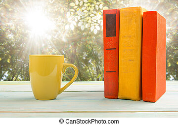 Stack of colorful books and cup at wooden table on natural...