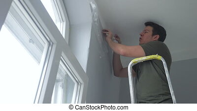 person attaching tape on wall - man standing on ladder and...