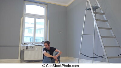 person starts work again - man sitting on floor and shows...