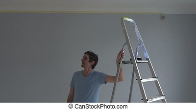 Man visualising something on the wall - worker standing next...