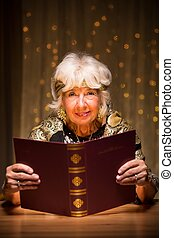Fortune teller with magic spellbook - Smiling elderly...