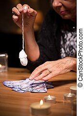 A pendulum and tarot cards - Fortuneteller using a pendulum...