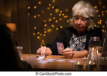 Woman reading cards - Eccentric elderly woman reading magic...