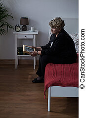 Sadness of widow - Widow sitting on a bed looking at her...