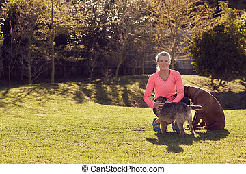 Athletic senior woman smiling in a park with her dogs