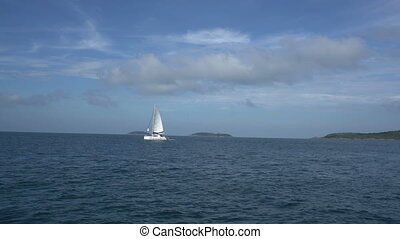 View of sailing yacht in sea and islands far away - View of...