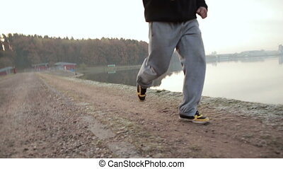 man running along the waterfront. slow motion - man trains...