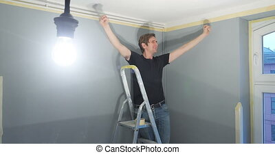 man renovating his new home - man standing on ladder and...