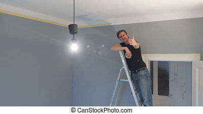 man showing thumbs on ladder - person standing on a ladder...