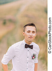 Portrait of handsome groom in bowtie Green field on...