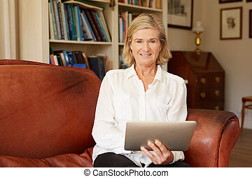 Portrait of a senior woman in living room with tablet