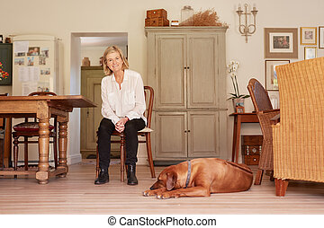 Senior woman smiling confidently in her home with dog - Low...