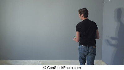 Man painting - person painting the words HOME on a wall in...