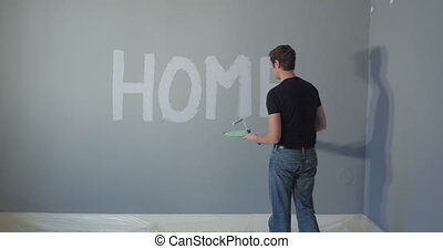 Man painting word on wall - person painting the words HOME...