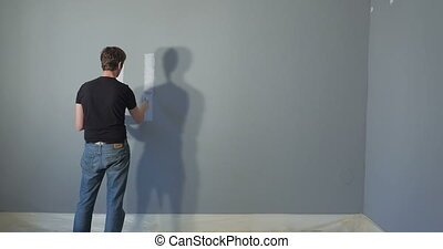 Man painting word on wall