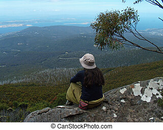 On top of the World - A woman sitting on a rock on the top...