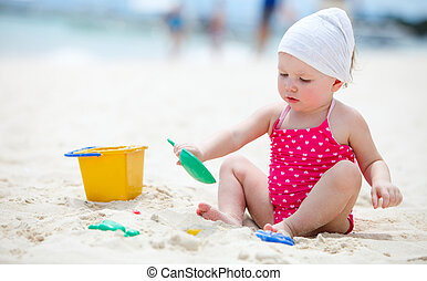 Beach vacation - Cute baby girl playing with beach toys on...