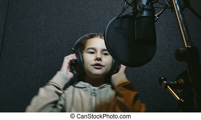 girl sings in the music studio - teen girl in headphones...