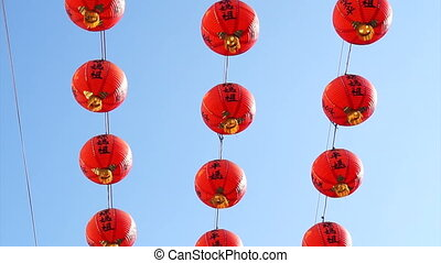 Row of red Chinese paper lanterns with ornate gold patterns...