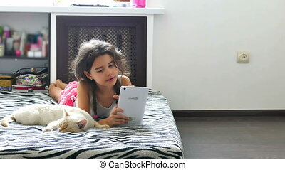 girl and tablet - girl teen playing tablet internet game...