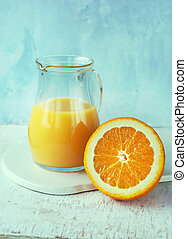 Orange juice in a pitcher and slice of orange on blue...