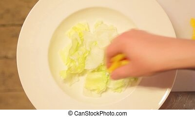 Chef puts sliced vegetables on a plate