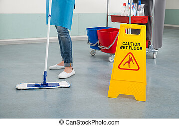 Female Janitor Mopping Corridor With Caution Sign - Close-up...
