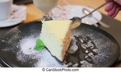 Breaking of a piece of cheesecake on a plate