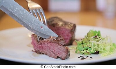Cutting red meat on a plate close-up.
