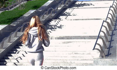 Young woman jogging up stairs in city - Young woman jogging...