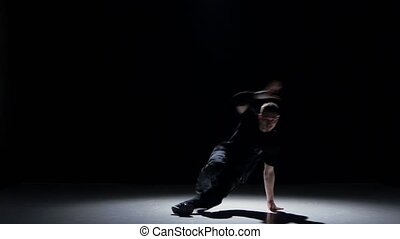 Talanted dancer man starts dancing breakdance on black -...