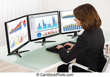 Businesswoman Working With Graphs On Computer - Young...