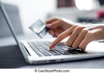 Woman holding credit card on laptop for online shopping